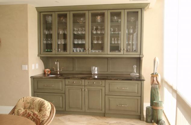 Custom Green cabinetry with glazing, custom bar area.